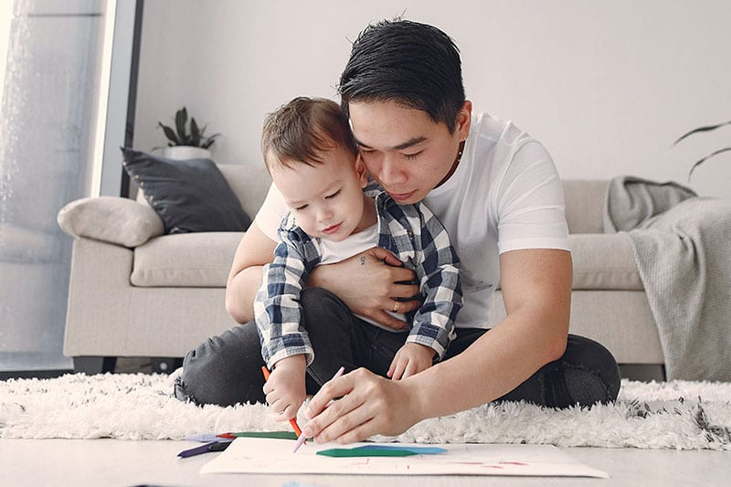 father and child drawing on the floor