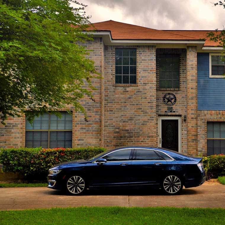 a blue car parked infant of a house in the suburbs