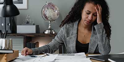 African American or hispanic woman looking at documents at her desk