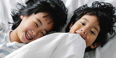 two asian kids in bed laughing