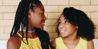 Two African American minor sisters looking at each other, smiling