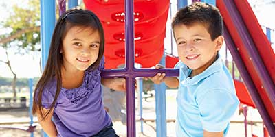 hispanic siblings, sister and brother, playing on the playground