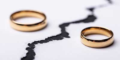 two wedding rings separated by a crack on the surface representing divorce