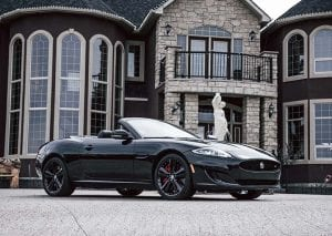 expensive sports car parked in front of mansion