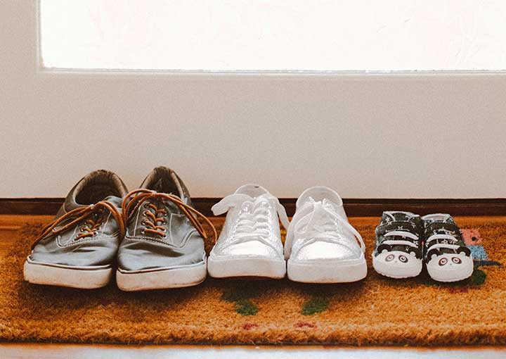 adult shoes and child shoes lined up on door mat