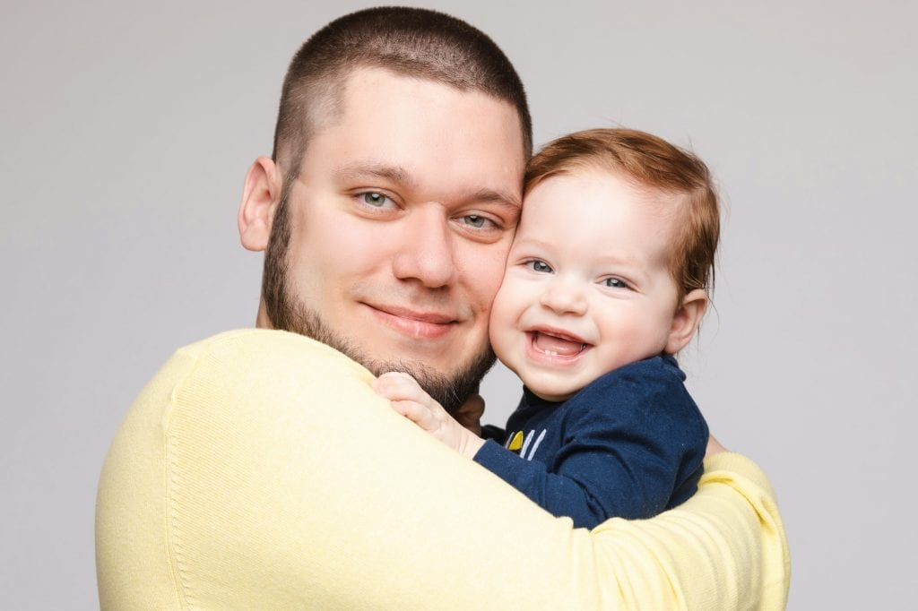 Portrait of happy father posing with lovely smiling child